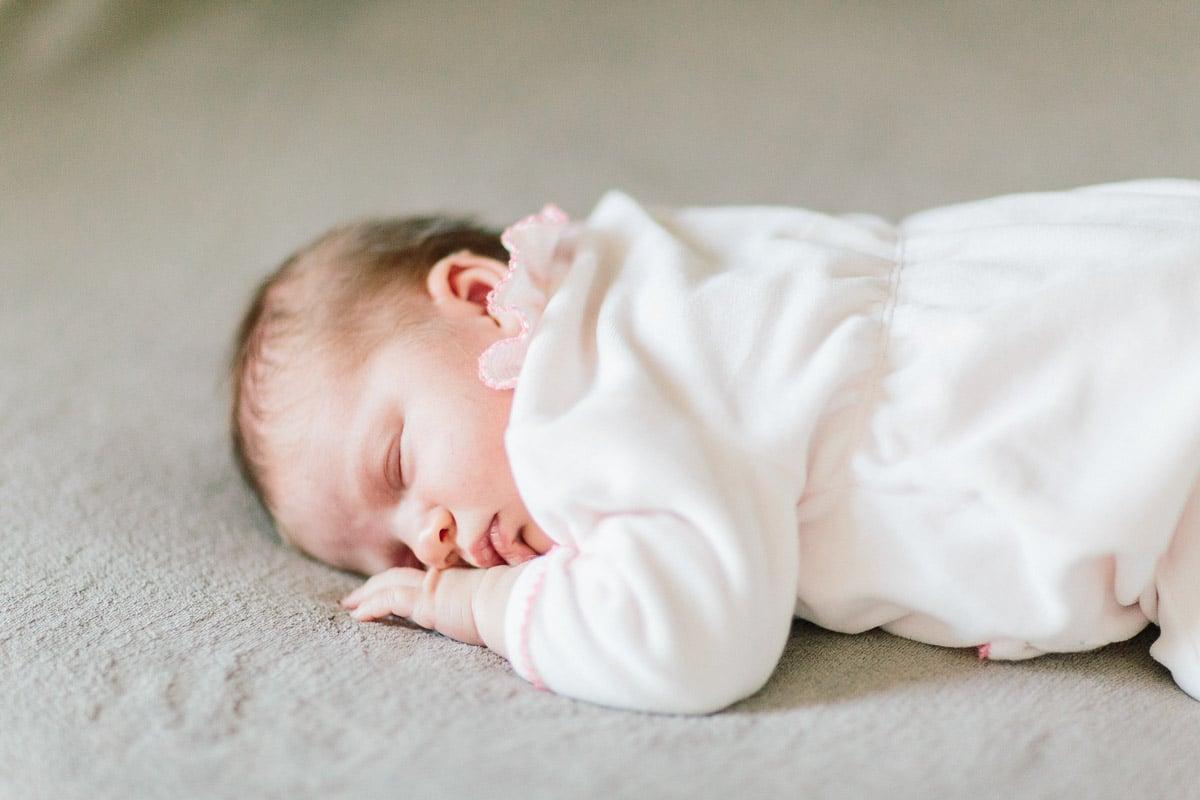 photos du bébé qui dort couché sur le lit lors d'une séance naissance en haute savoie