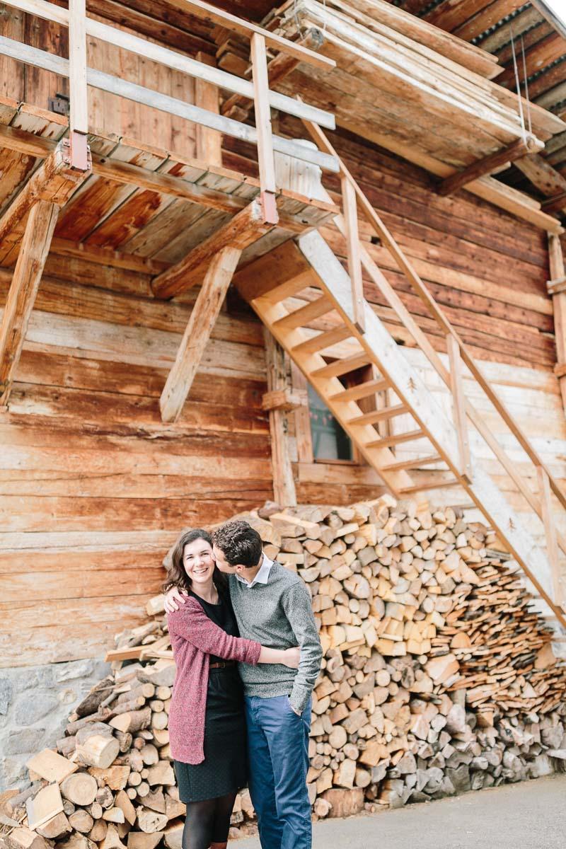 photo d'un couple enlacé devant un chalet pendant un engagement à Annecy, haute Savoie en montagne