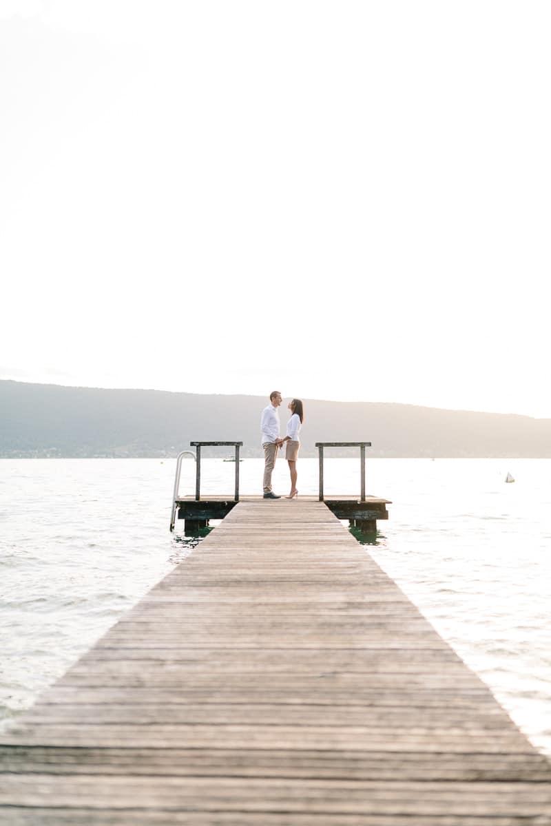 photo d'un couple face a face sur un ponton pendant un engagement à Annecy, haute Savoie au bord du lac