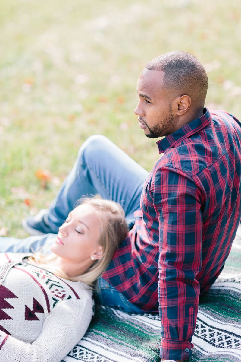 photo d'un couple allongés sur une couverture dans les champs pendant un engagement à Annecy, haute Savoie