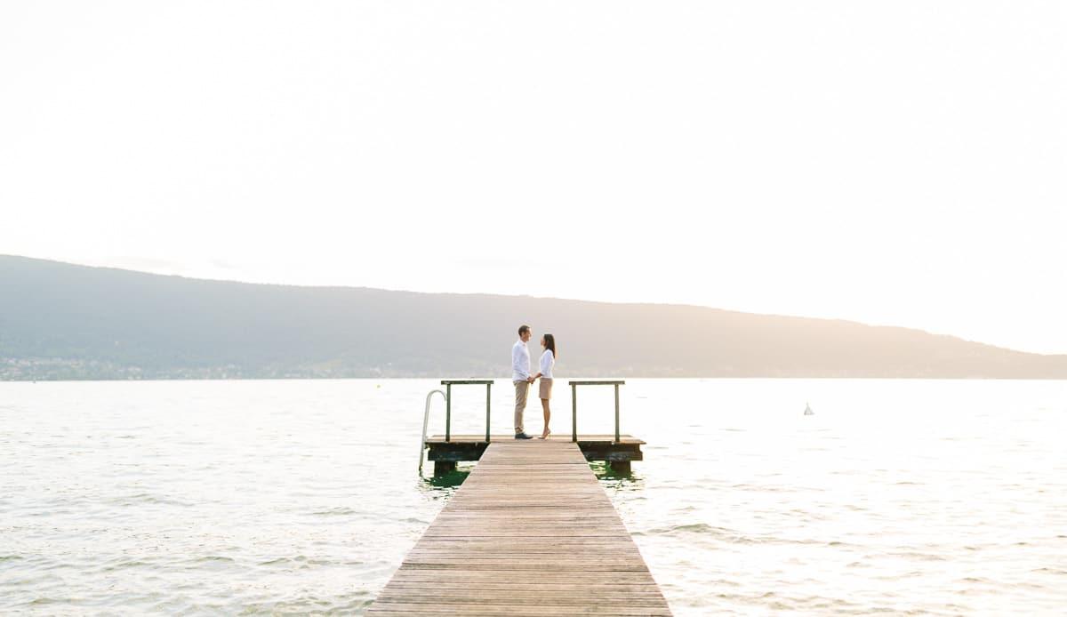 photo à annecy d'un couple lors d'une séance engagemnt au bord du lac au couché du soleil