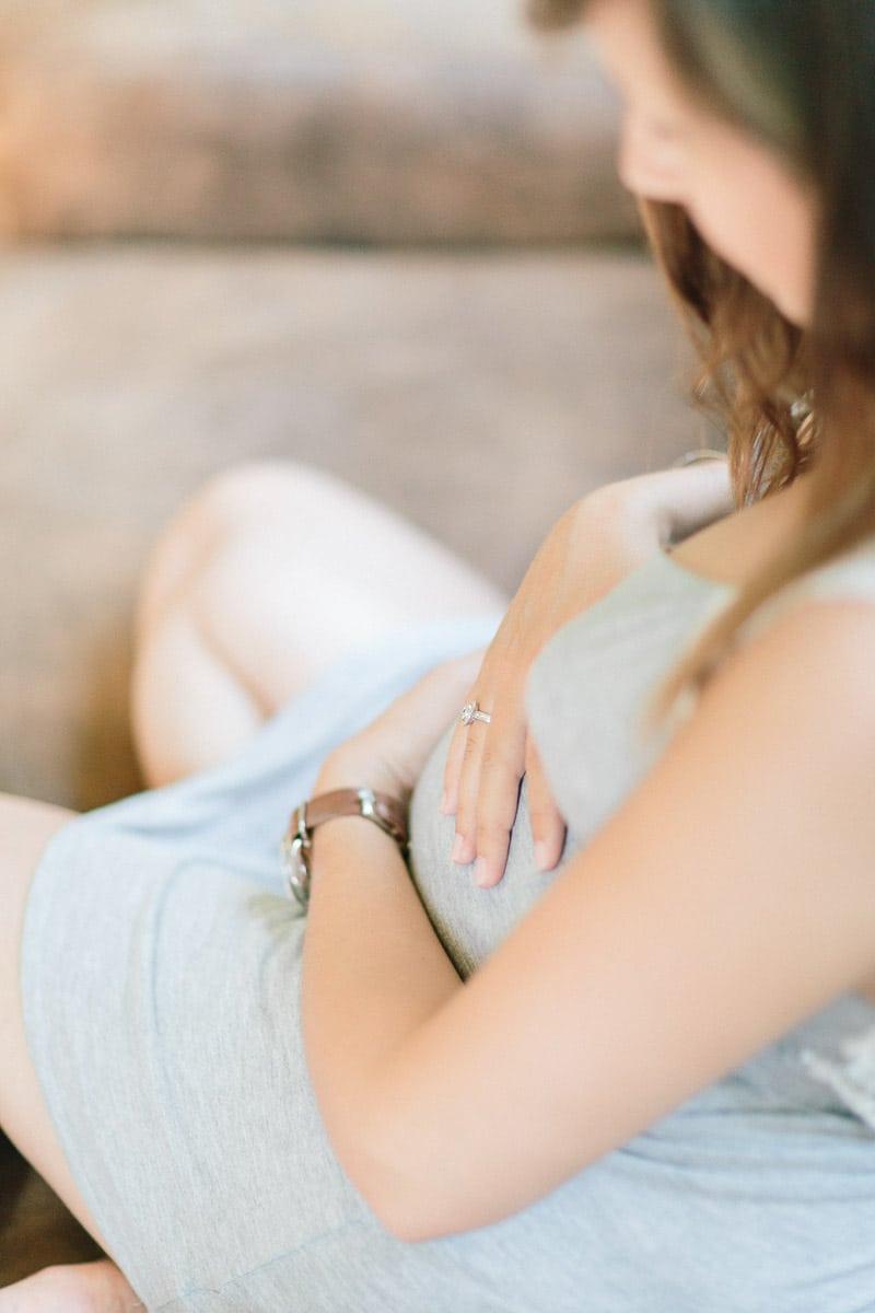 Photos d'une séance grossesse à Aix les Bains vers Annecy et Genève la future maman est assise sur le canapé