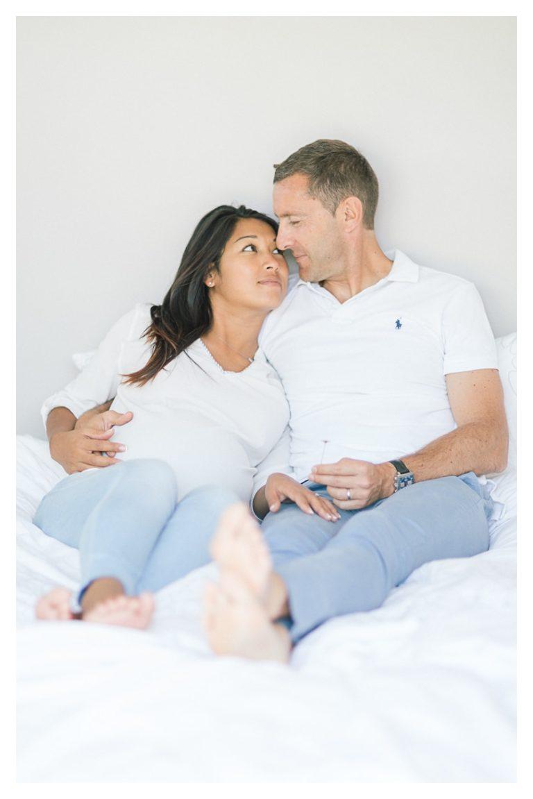 Photo séance grossesse maternité à Annecy en couple couchés sur le lit