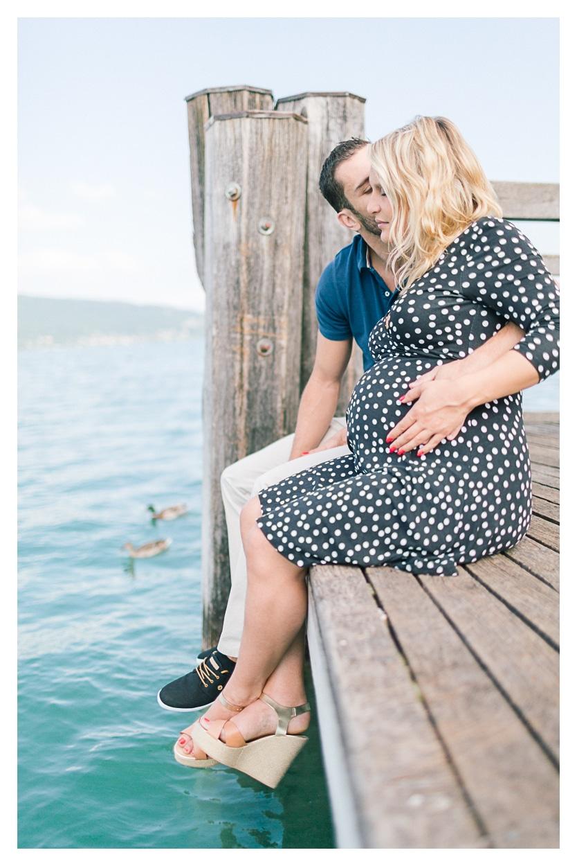 Photo séance grossesse maternité à Annecy couple assis sur un ponton au bord de l'eau