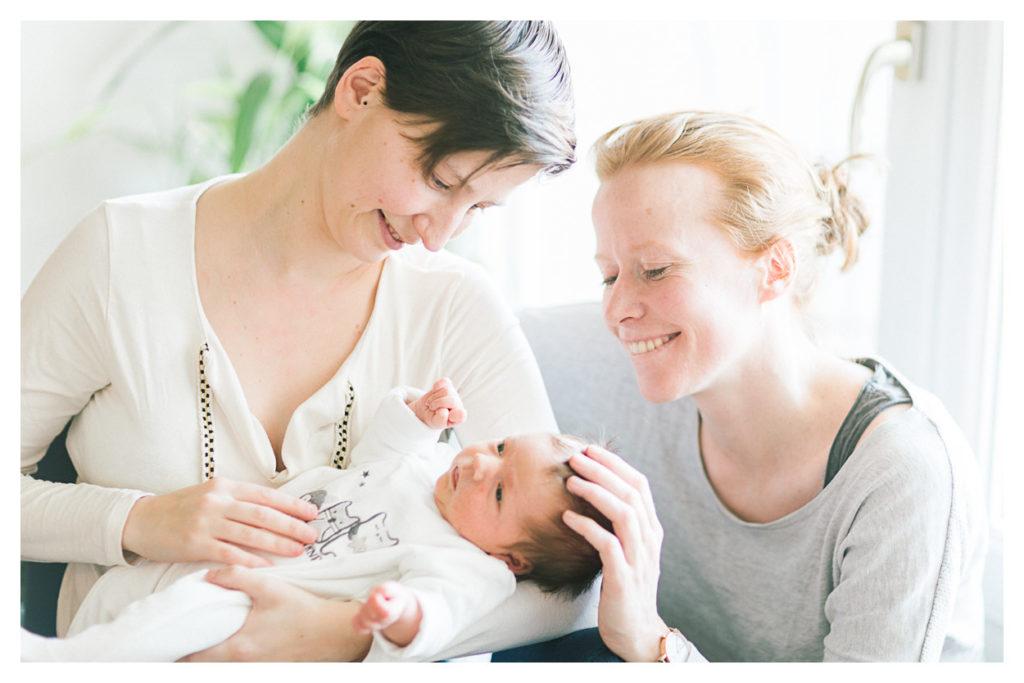 Photographe bébé à Genève en Suisse. Deuxièmement, photo du couple de maman qui porte leur fille dans les bras lors du shooting photo de la séance naissance