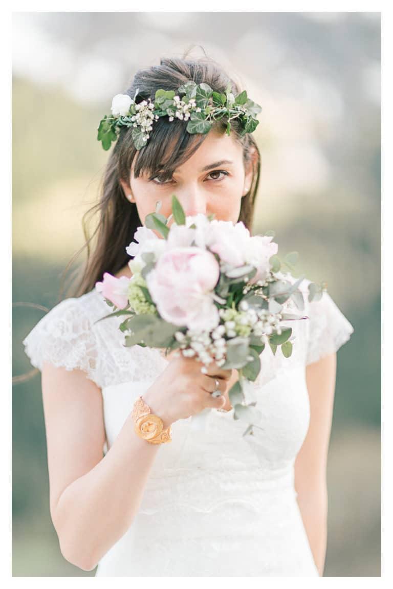 Portrait de la mariée, alors qu'elle est cachée derrière son bouquet de fleurs. Mariage intime et bohème chic en montagne