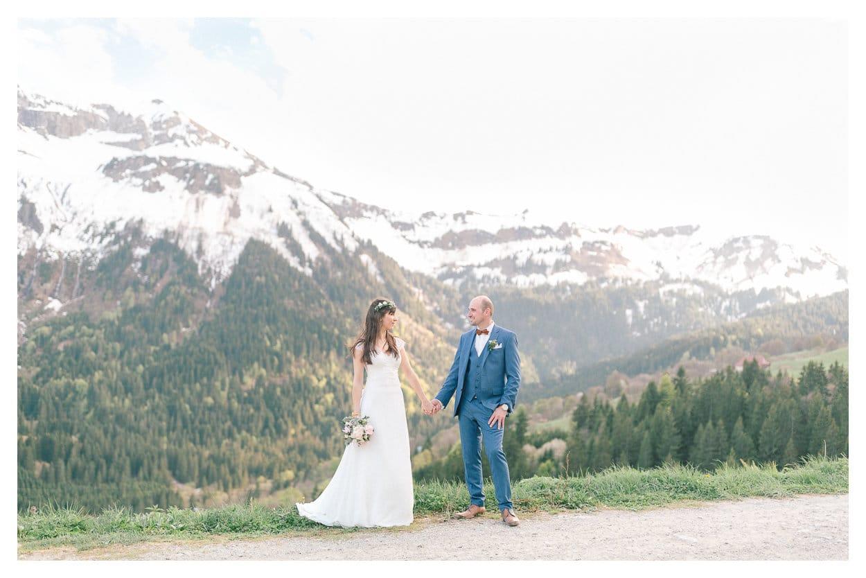 Photo des époux après la cérémonie. Ils se tiennent la main devant la montagne sous la neige lors de leur mariage intime à Annecy